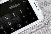 A calculator next to financial documents — Stock Photo
