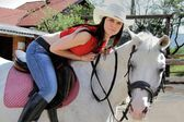 Beautiful young brunette woman ride black horse — Stock Photo