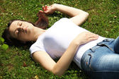 Beautifull woman is lying and resting in the grass — Stock Photo