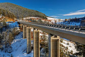 Mountain bridge in winter with snow and blue sky — Stock Photo