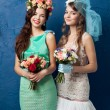 Two beautiful brides with flower wreath and bouquet on blue background — Stock Photo #42281559