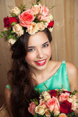 Beauty portrait of woman with flower wreath and bouquet on wood background. Bride. — Foto de Stock