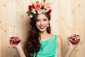 Beauty portrait of cheerful woman with flower wreath and pomegranate on wood background — Stock Photo