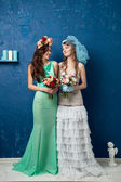 Two beautiful brides with flower wreath and bouquet on blue background — Stock Photo