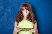 Surprised young woman holding book on blue background — Stok fotoğraf