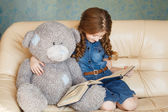 Cute little girl reading with teddy bear — Stock Photo
