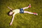 Little girl lie on the grass — Stock Photo