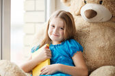 Little girl holding a book on windowsill with big toy — Stock Photo