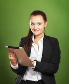 Business woman holding tablet pc on green background — Stock Photo