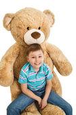 Young boy sitting at a big teddy bear  — Stock Photo