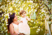 Mulher feliz e criança no desabrochar da primavera garden.mothers dia — Fotografia Stock
