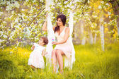 Happy woman and child in the blooming spring garden.Mothers day — Стоковое фото