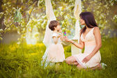 Happy woman and child in the blooming spring garden.Child kissi — Stock Photo