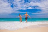 Happy couple running on the beach — Stock Photo
