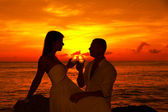 Romantic couple at tropical beach with sunset in the background — Stock Photo