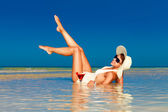 Young woman in straw hat laying at the tropical beach and enjoyi — ストック写真