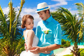 Bride and groom having fun on a tropical beach under the palm tr — Stock Photo