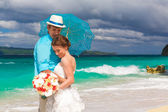 Happy bride and groom with blue umbrella and wedding bouquets on — Stock Photo
