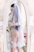 Beautiful young bride in the veil, and with garter stands in fro — Stock Photo