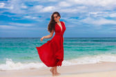 Beautiful woman in a red dress  standing on the sea coast — Stock Photo