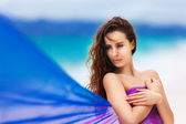 Beautiful young girl in a purple cloth on a tropical beach — Stockfoto