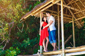 Young beautiful loving couple in tropical hut — Stock Photo