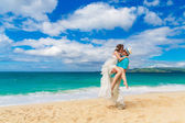 Bride and groom kiss on a tropical beach — Stock Photo
