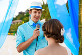 Wedding ceremony on a tropical beach in blue . The groom speaks  — Stock Photo