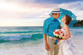 Wedding. Bbride and groom on the tropical coast at sunset — Stok fotoğraf
