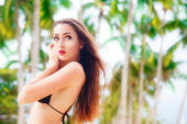 Beautiful young woman with long hair in black bikini relaxes und — 图库照片