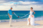 Happy bride and groom having fun on a tropical beach. Just marri — Stock Photo