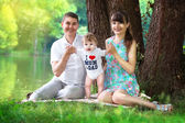 Happy family, mom, dad and little son having fun in the park on  — Stock Photo