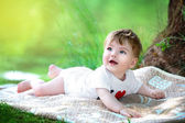 Happy little baby having fun in the park on the lake shore backg — Stock Photo