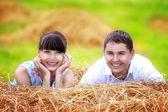 Влюбленные счастливы весело в поле на стоге сена. Лето — Стоковое фото