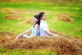 Coppia di innamorati felici divertendosi in un campo in un pagliaio. estate — Foto Stock