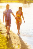 Happy couple in love walking on the beach. Summer vacations conc — Stock Photo