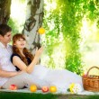 Happy and young pregnant couple hugging in nature enjoying summe — Stock Photo #48819705