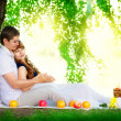 Happy and young pregnant couple hugging in nature enjoying summe — Stock Photo #48819711