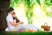 Happy and young pregnant couple hugging in nature enjoying summe — Stock Photo