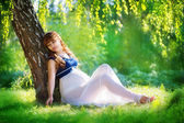 Young pregnant woman relaxing in park outdoors, healthy pregnanc — Stock Photo