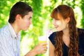 Beautiful Young Couple Drinking Juice from one Glass with Colore — Stock Photo