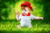 Happy little baby in red hat having fun in the park on solar gla — Stockfoto