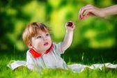 Happy baby have fun in the Park on a Sunny meadow with cherries. — Stock Photo
