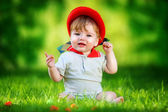 Happy little baby in red hat having fun in the park on solar gla — Stock Photo
