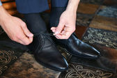 Businessman putting on black leather shoes for work. — Stockfoto