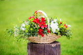Floral arrangement with strawberries in a basket on the grass. — Stock Photo