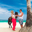 Young couple in love walking with the horse on a tropical beach. — Stock Photo #51490669