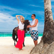 Young couple in love walking with the horse on a tropical beach. — Stock Photo #51490671
