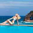 Young beautiful blonde girl is next to the pool. Tropical sea in — Stock Photo #51490707