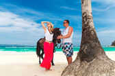 Young couple in love walking with the horse on a tropical beach. — Stock Photo